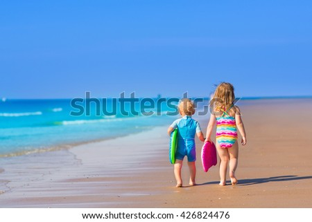 Little boy and girl with surfing boards playing on tropical ocean beach. UV and sun protection for young children. Summer water fun for surfer kids. Child learning to swim and surf with body board. - stock photo