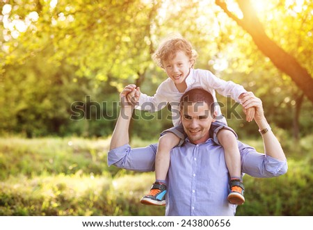 Little boy and his dad enjoying their time together outside in nature - stock photo