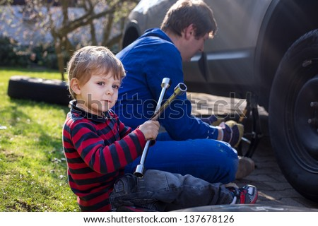 Little boy and his father changing wheel on car with pneumatic wrench - stock photo