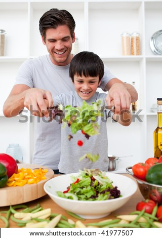 Little boy and his father cooking in the kitchen - stock photo