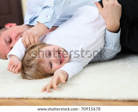little boy and his father playing together at home on the floor