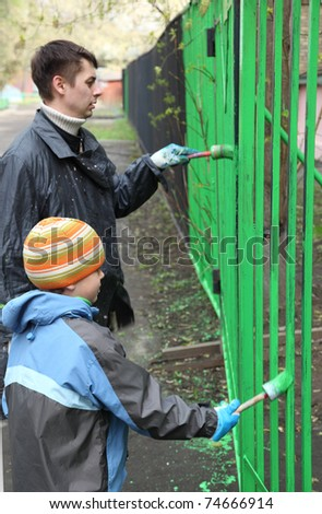 Little boy and his father stand back and dye fence by green color on community work day, boy in focus
