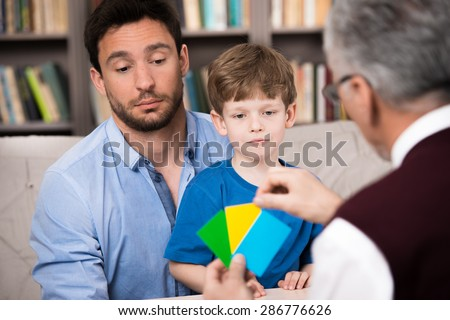 Little boy and his father talking with psychologist. Psychologist making test with boy. There are many books in psychologist office - stock photo