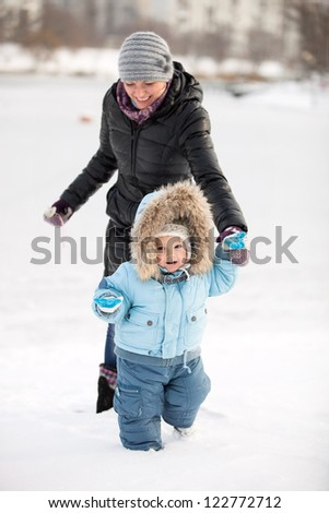 Little boy and his mom having fun on a winter day - stock photo