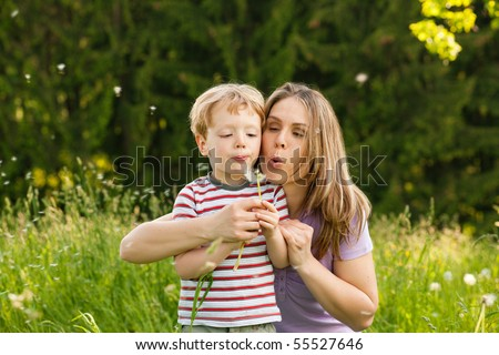 Little boy and his mother blowing dandelion seed for a whish on a meadow outdoors in summer