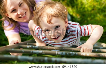 Little boy and his mother climbing up a ladder from a meadow, they want to reach their tree house (house not to be seen) - stock photo