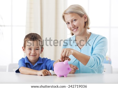 Little boy and his mother inserting money into piggy bank. Mother teaching her son about savings. - stock photo