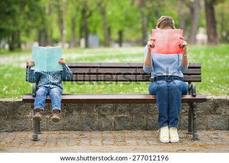 Little boy and his mother sitting on a park bench reading books - stock photo