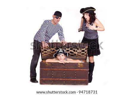 Little boy and his parents in the form of pirates, the boy in the chest with treasures. - stock photo