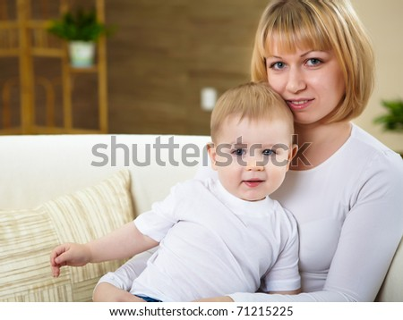 little boy and his young mother together at home sitting on the sofa - stock photo