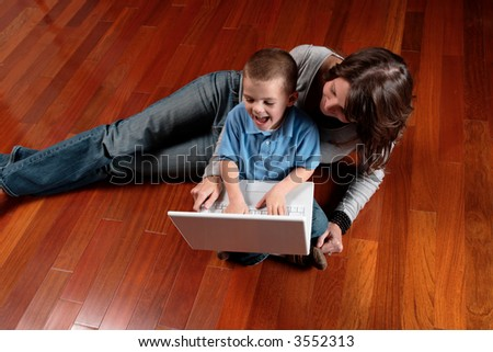 little boy and mom on floor laughing while looking at a laptop computer - stock photo