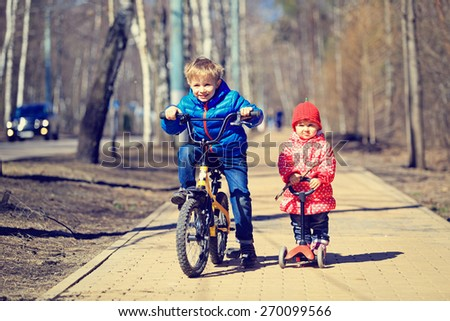 little boy and toddler girl, brother and sister, riding bicycle and scooter outdoors - stock photo