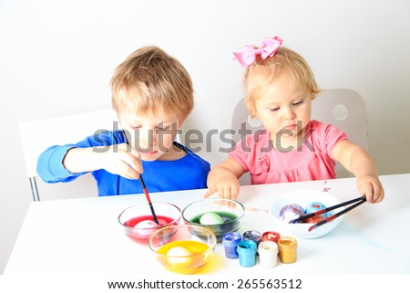 little boy and toddler girl painting eggs for easter holiday - stock photo