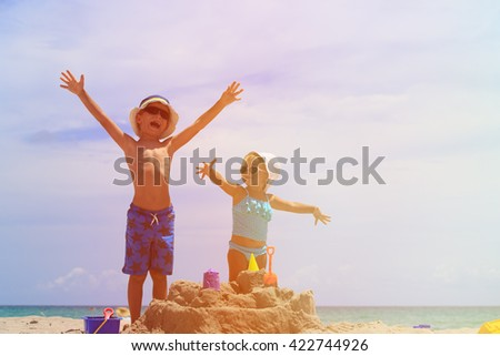 little boy and toddler girl play with sand on beach - stock photo