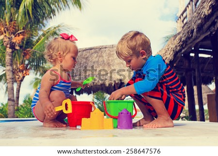 little boy and toddler girl playing in swimming pool at beach - stock photo