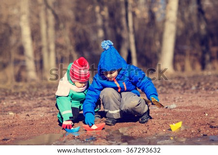 little boy and toddler girl playing with water in spring - stock photo