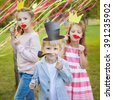little boy and two girls posing with paper masks on a cheerful children's holiday. - stock photo