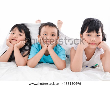 little boy and two little girl laying on in studio