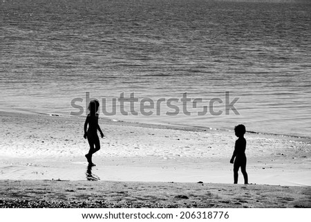 Little boy ang girl silhouettes in counter light on a river bank, monochrome - stock photo