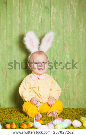 Little boy as a Easter rabbit on the grass with colorful eggs - stock photo