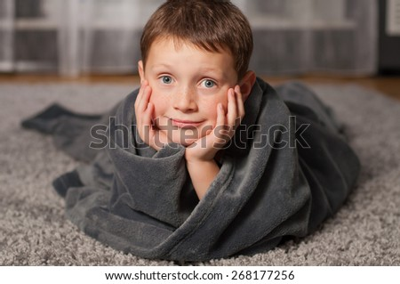 little boy at home on the carpet in plaid - stock photo