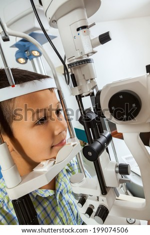 Little Boy At Ophthalmologist Looking Into Eye Test Machine