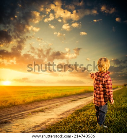 little boy at rural road sunset pointing to horizon - stock photo