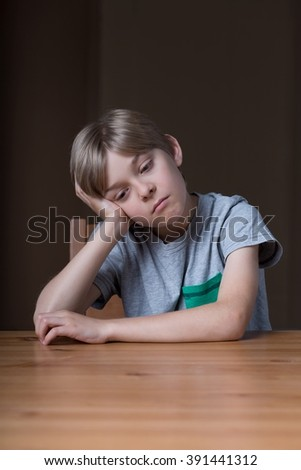 Little boy at the table feeling sad and gloomy - stock photo