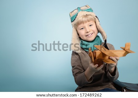 Little boy aviator dreaming and playing with wooden handmade toy plane, vintage toned - stock photo