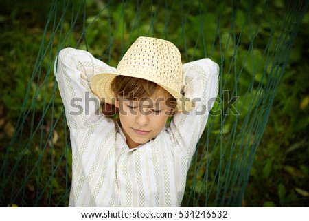 Little boy blond in a straw hat with closed eyes lying on the hammock. Children and nature.