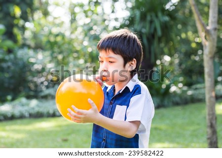 Little boy blowing a orange balloon in park on a sunny day. - stock photo