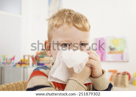 Little boy blows her nose - Stock Image
