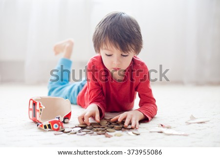 Little boy, breaking his piggy bank, emptying all saved money to buy gift for mother's day - stock photo