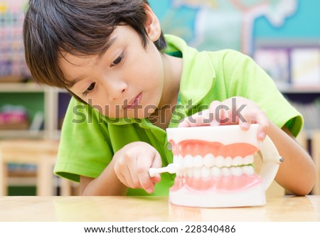 little boy brushing Fake Jaw learn how to brush teeth - stock photo