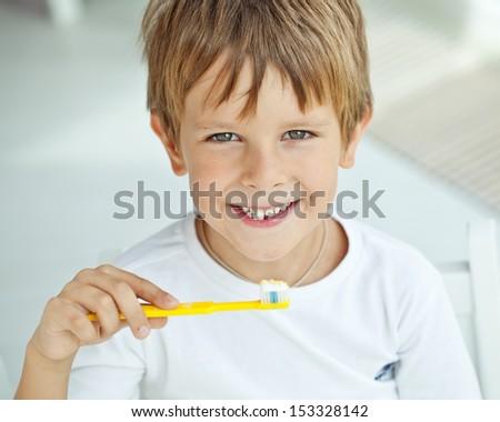 Little boy brushing his teeth - stock photo