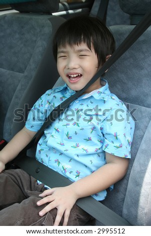Little boy buckle up seat-belt sitting in the car - stock photo