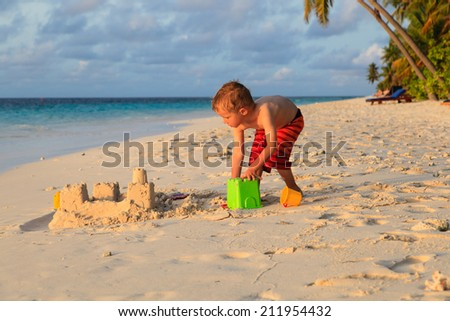 little boy building sand castle on sunset tropical beach - stock photo