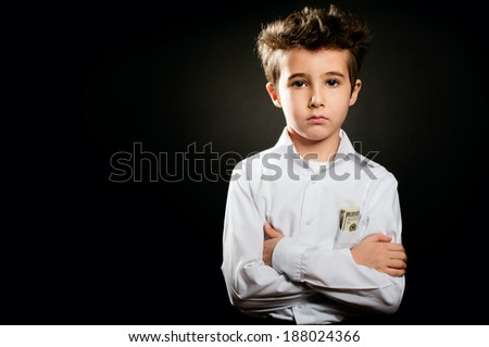 Little boy businessman in white shirt portrait in low key with arms crossed - stock photo