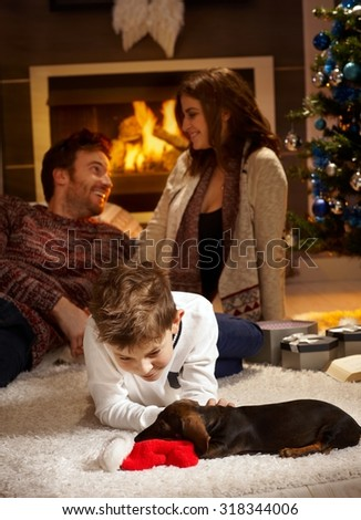 Little boy caressing dachshund puppy receiving for christmas, parents at background. - stock photo