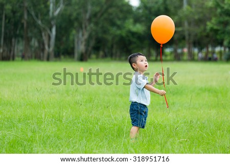 Little boy catch with balloon - stock photo