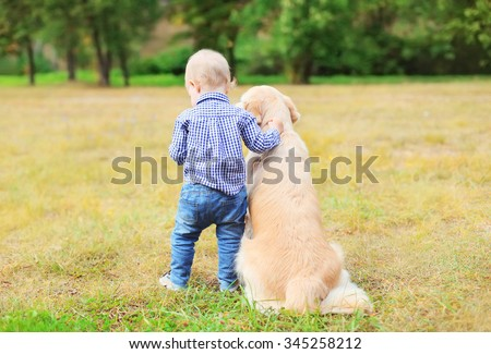 Little boy child and Golden Retriever dog together outdoors, back view - stock photo