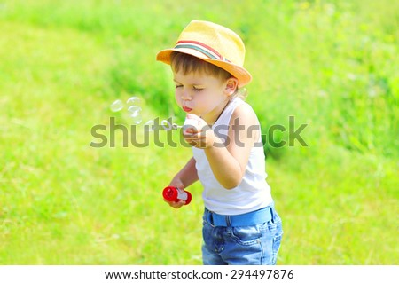 Little boy child blowing soap bubbles outdoors in sunny summer day - stock photo