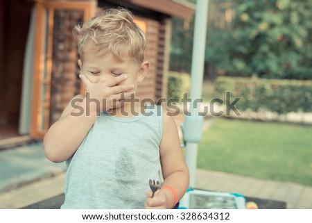 little boy child laughing with his hand covering his face, he is trying to eat his meal with a fork, but it just won't work - stock photo