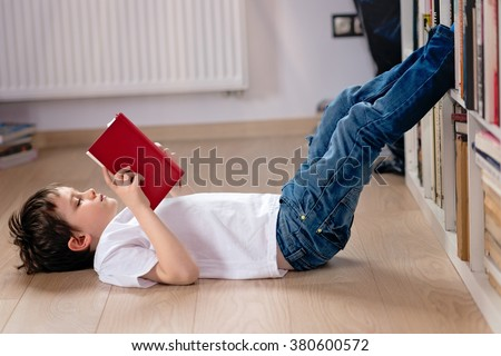 Little boy child reading a book in the library. He lies on the floor. Legs on bookshelf - stock photo