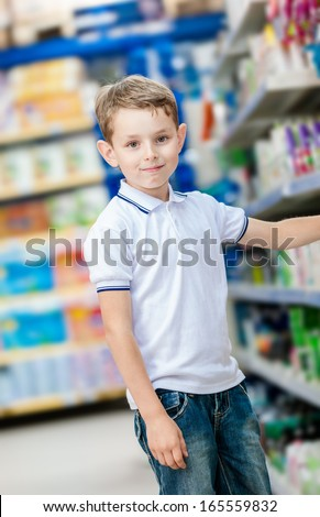 Little boy chooses cosmetics on the shelves of the shop