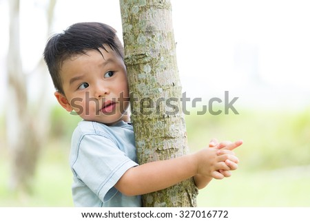Little boy climb up on the tree - stock photo