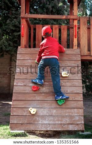 Little boy climbing at playground, outdoor - stock photo