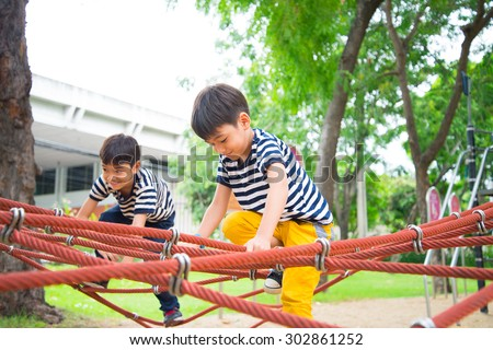 Little boy climbing rope at playground - stock photo