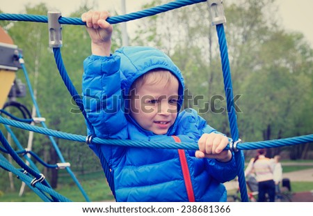 little boy climbing rope on the playground outdoors - stock photo