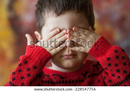 little boy closed his eyes with hands, abstract background - stock photo
